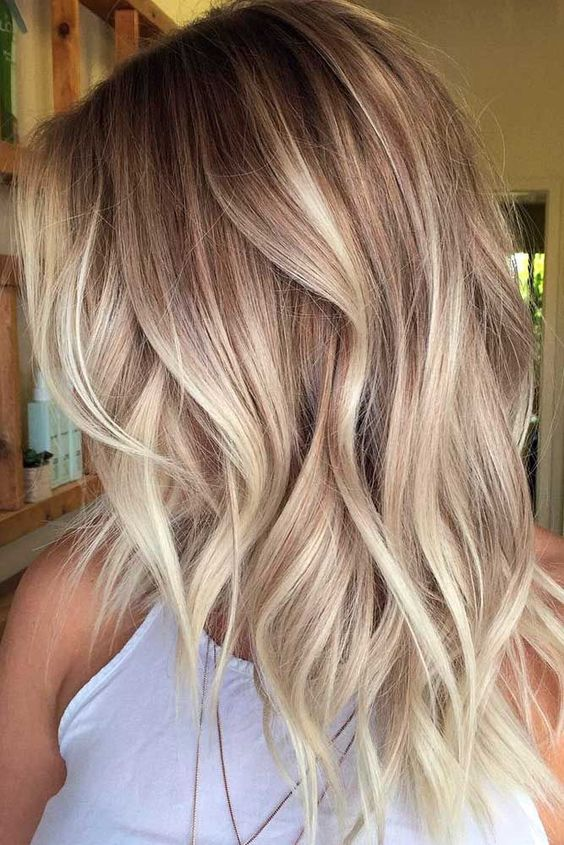 blonde balayage on wavy layered chestnut hair is a cute and girlish idea