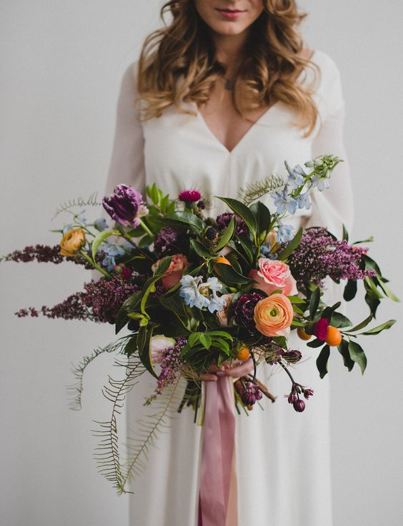 a colorful wedding bouquet in purple, peachy yellow, blue and pink looms and much greenery