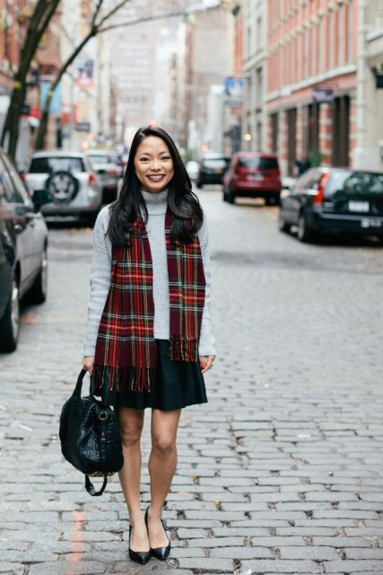 With gray turtleneck sweater, mini skirt, flats and black bag