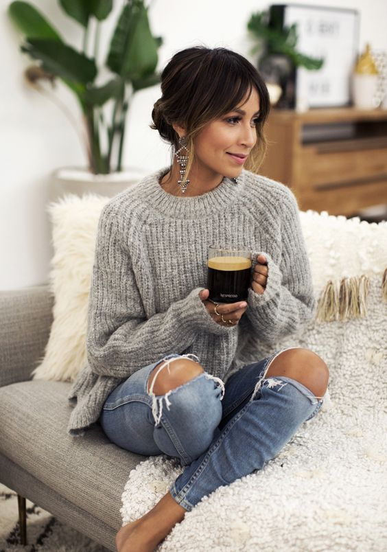 a comfy grey sweater with a high neckline, ripped jeans and statement earrings