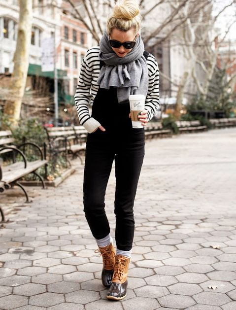 a striped top, a black overall, snow boots and a comfy cashmere scarf