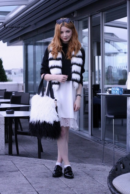 With black shirt, white skirt, flat boots and fur bag