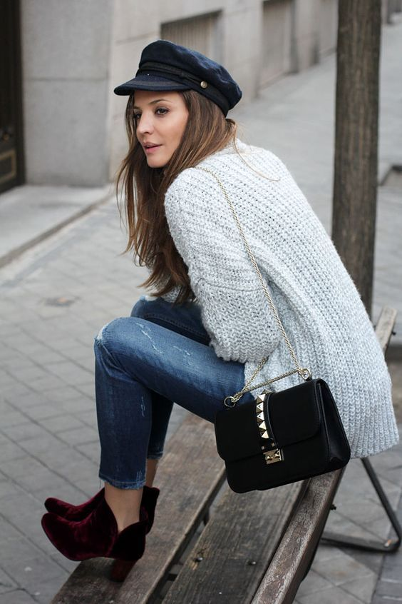 cropped ripped denim, plum-colored velvet booties, a grey chunky knit sweater and a black cap