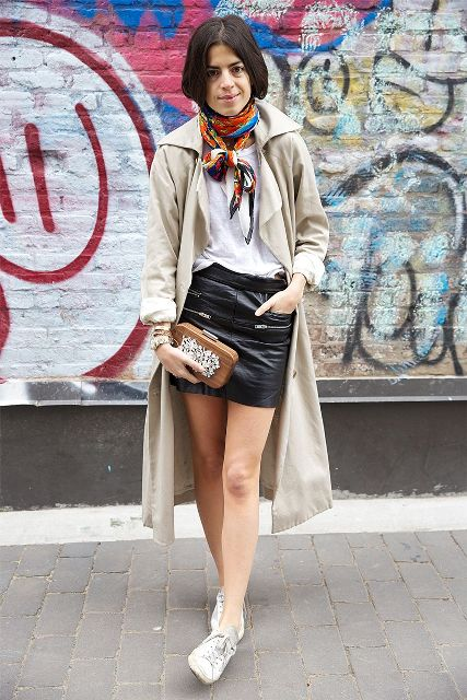 With white t-shirt, leather skirt, white sneakers, beige trench coat and clutch