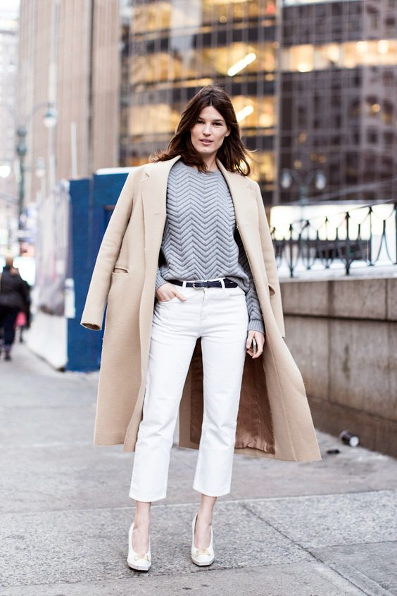 white cropped pants, a grey sweatshirt, white heels and a tan coat