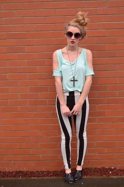 With pastel colored top and heeled boots