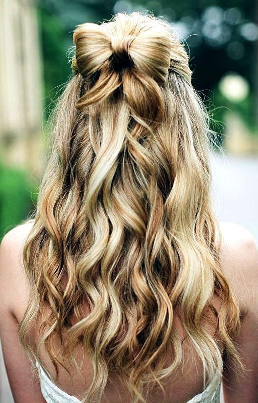 a fun half updo with waves and a bow of hair for those who want a playful look