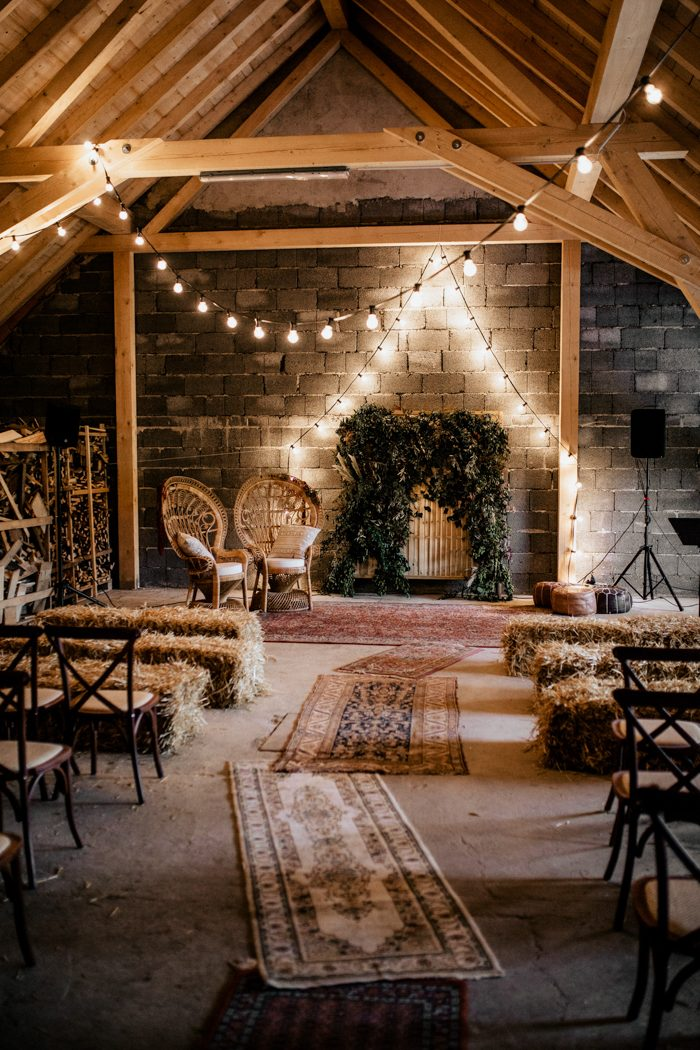 The wedding ceremony space was done with hay, boho rugs, boho woven chairs and a lush greenery and feather backdrop