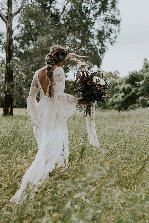 a boho lace wedding gown with bell sleeves, a cutout back and a train