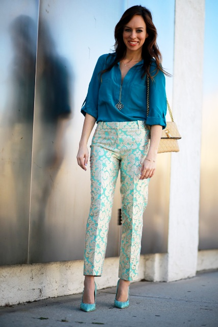With teal blue shirt, beige bag and turquoise pumps