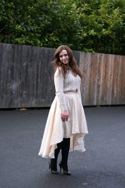 With white sweater, black tights and pumps