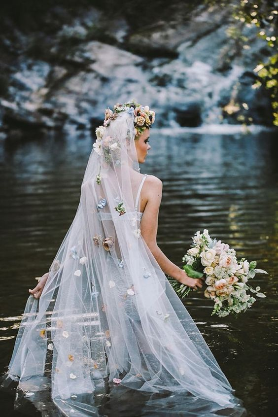 a long veil with a faux flower halo on top and pastel-colored faux blooms all over the veil