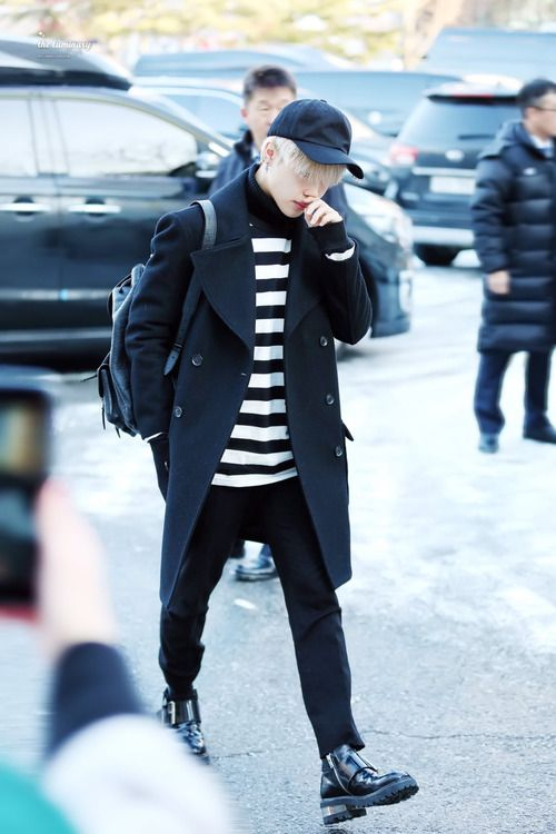 black pants, a striped top, a black coat, black boots and a baseball cap