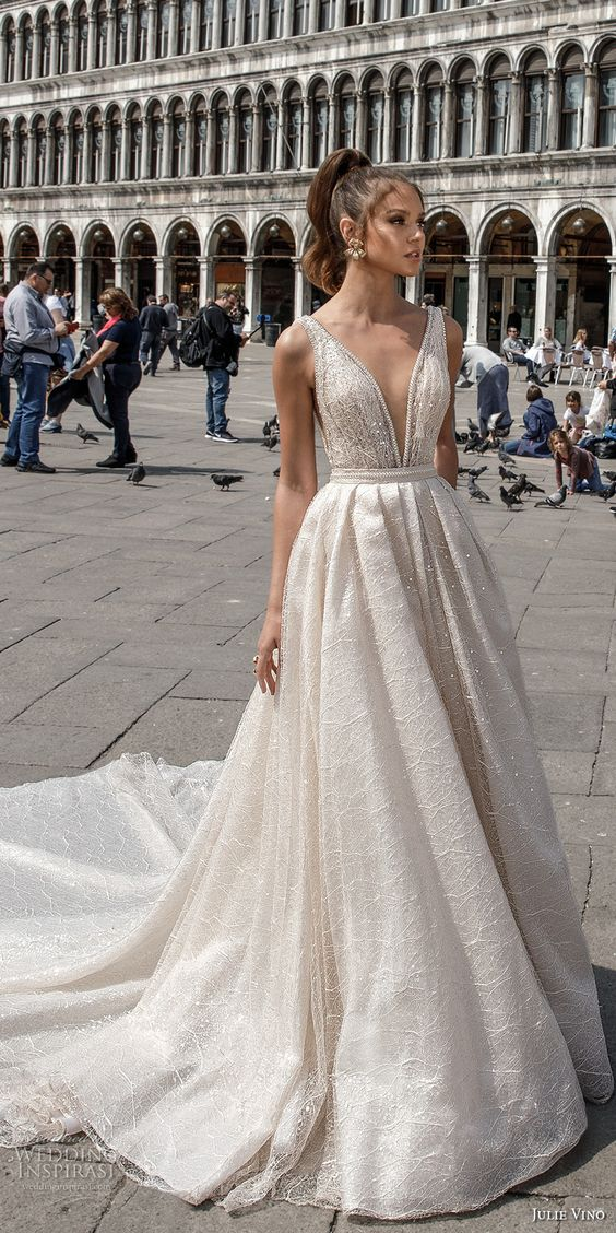 a wide strap plunging neckline wedding ballgown with heavy embellishments and a train by Julie Vino