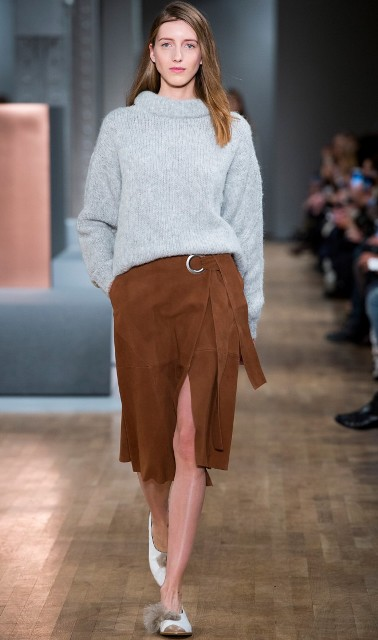 With oversized sweater and flats
