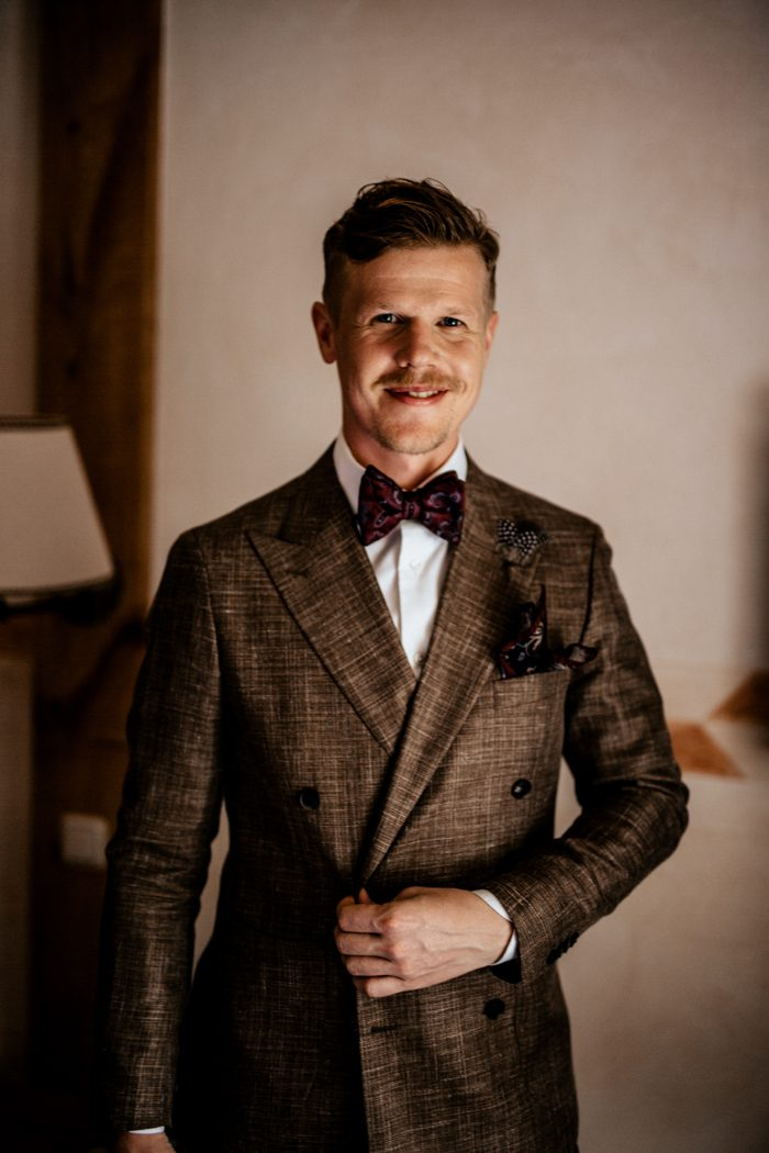 The groom was wearing a brown jacket, black pants, a white shirt and elegant burgundy printed accessories