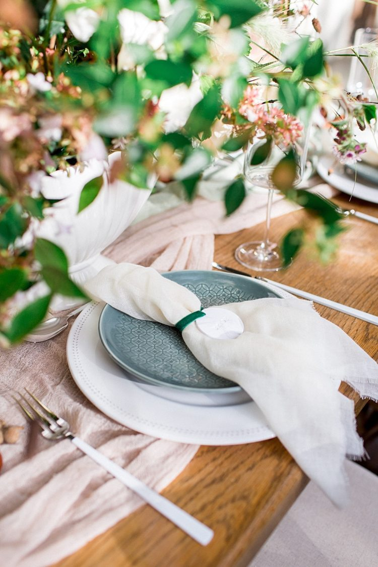 The table was decorated with lush florals, a blush runner and ivory napkins, green plates and neutral chargers