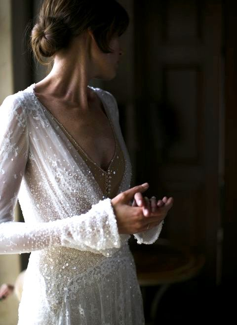 a heavily embellished lace applique wedding dress with bell sleeves and a nude buttoned bodice