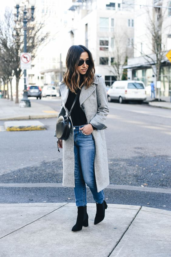 a black top, blue straight jeans, black chelsea boots and a grey coat