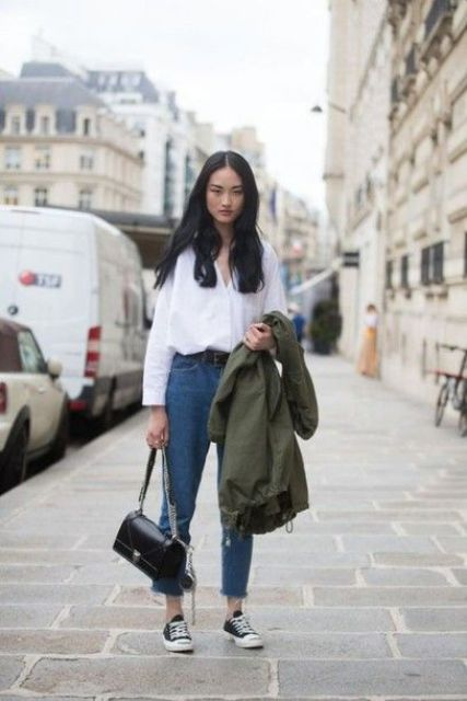 a white shirt, blue high waisted jeans, black sneakers and an olive green jacket