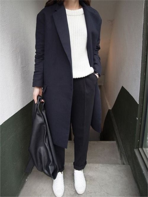 black trousers, a white chunky knit sweater, a black coat and white sneakers