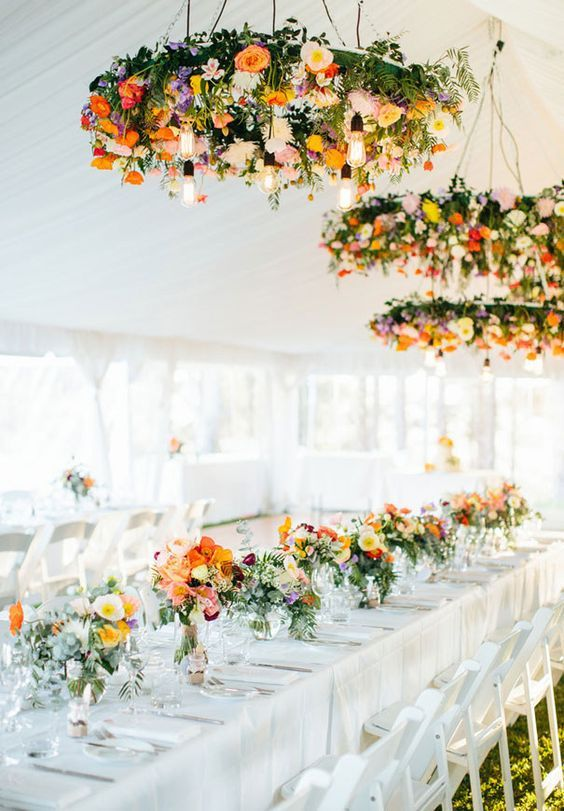 bold floral chandeliers over the tables and matching blooms on them
