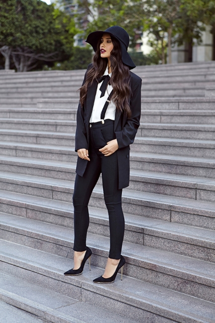 With white button down shirt, black pumps, long blazer and wide brim hat
