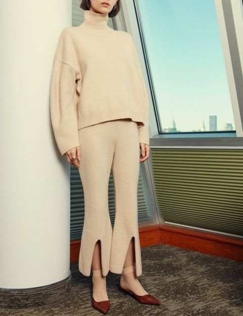 With beige oversized sweater, beige socks and suede shoes