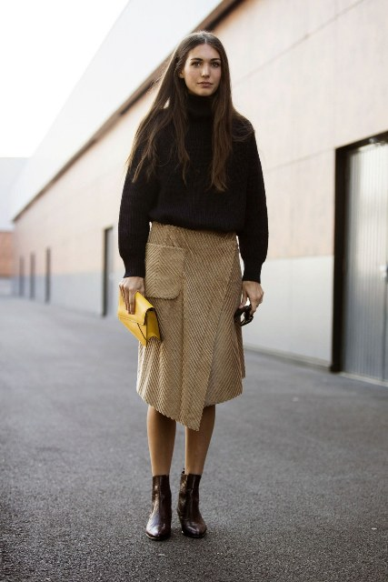 With oversized turtleneck, yellow clutch and ankle boots