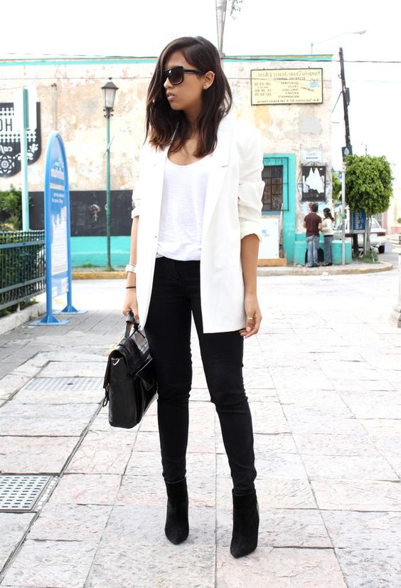 black skinnies, black suede booties, a white top and a long blazer and a black bag