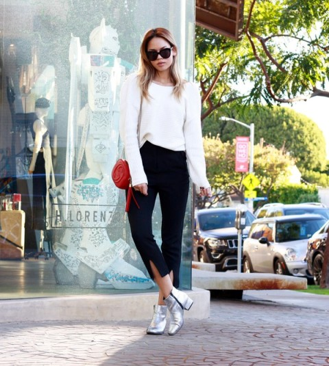 With white oversized sweatshirt, silver ankle boots and red bag