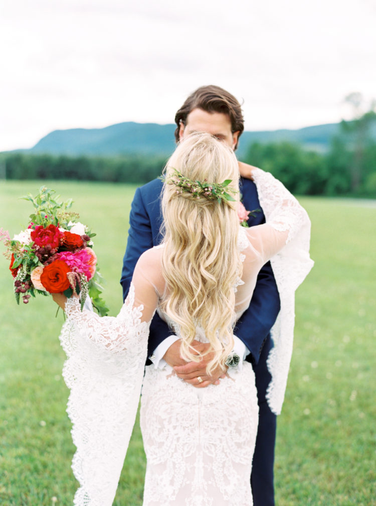 a lace sheath wedding dress with wide bell sleeves and a boho feel