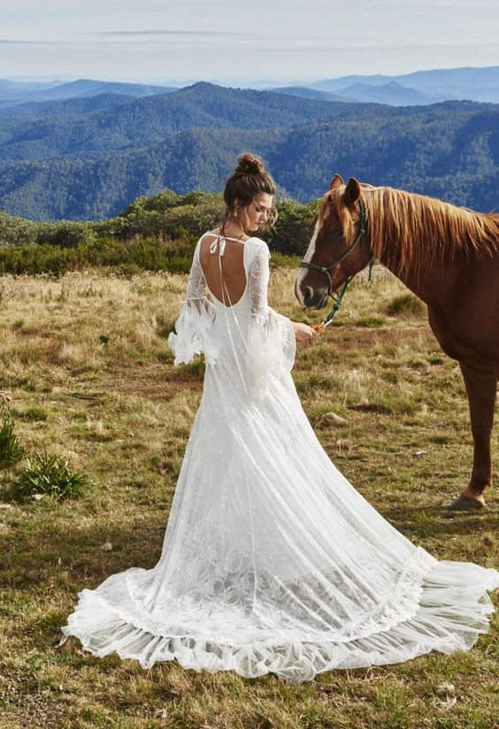 country wedding dress with a cutout back, bell sleeves, a full overskirt and a bow on the back