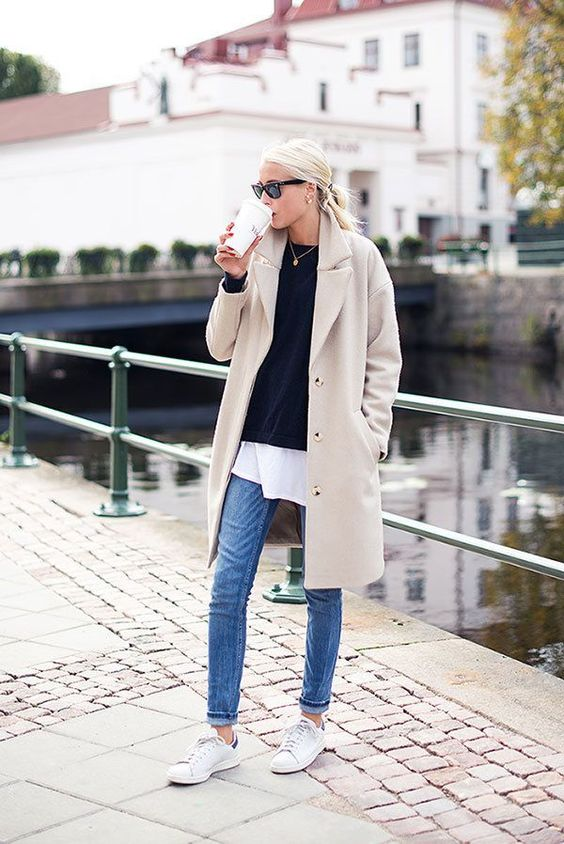 blue jeans, a white tee, a black pullover, white sneakers and a tan trench