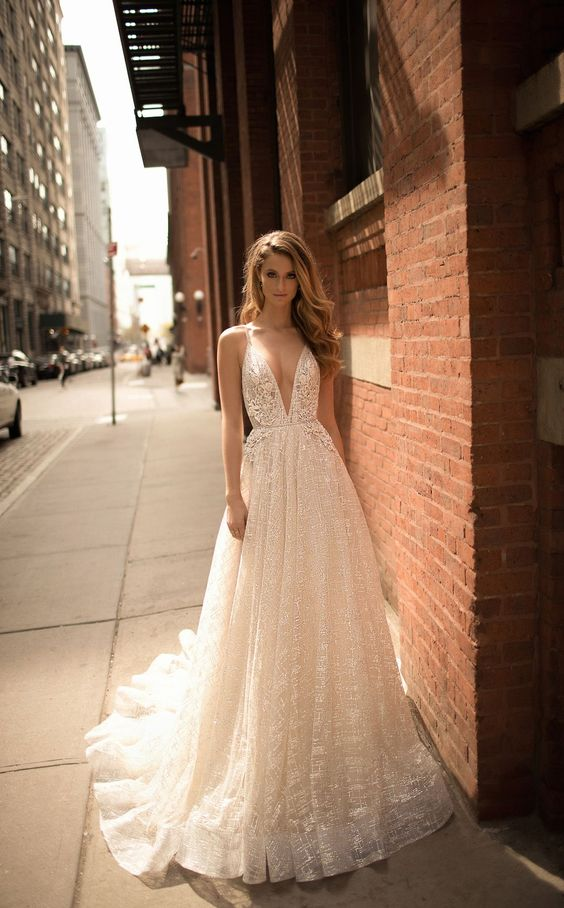 a sparkling deep plunging neckline wedding dress with a train and straps by Berta