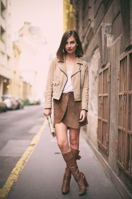 With top, beige jacket, clutch and brown high boots