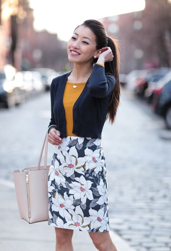 a floral print knee skirt, a mustard top, a cropped navy cardigan and a neutral bag