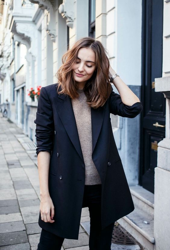 a black double breasted long blazer, a neutral crocheted top and black skinnies