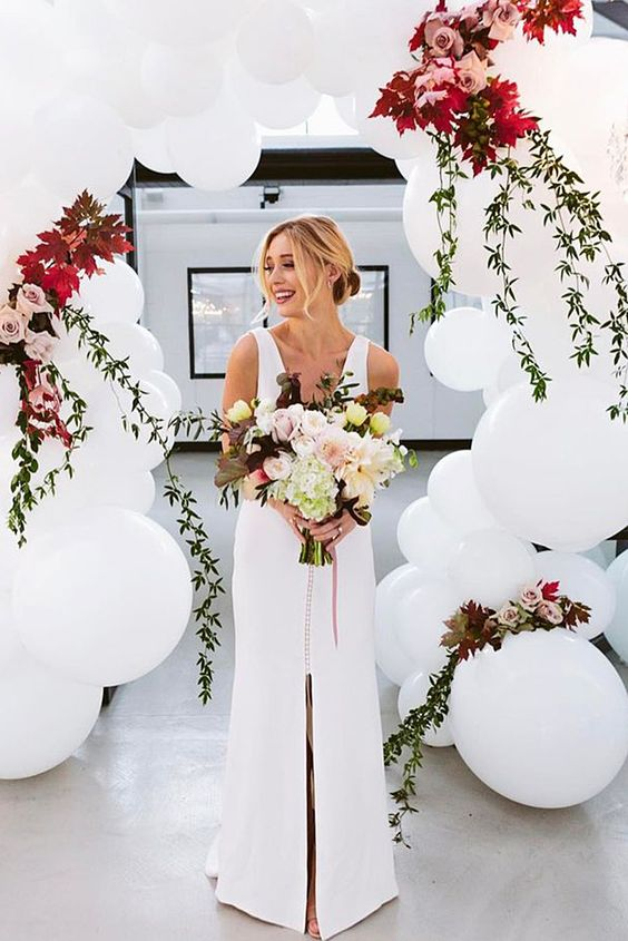 a gorgeous wedding arch of white balloons and bold blooms for a modern ceremony