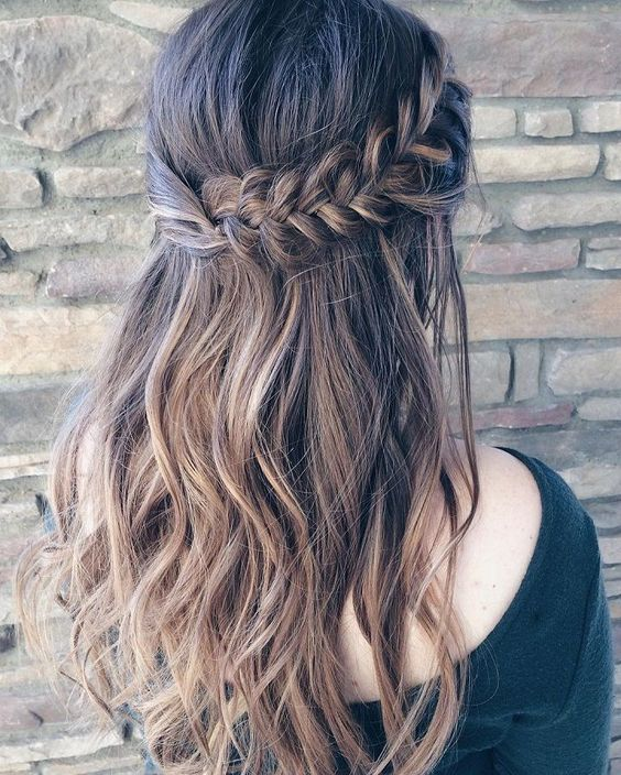 a wavy half updo with a thick fishtail braid on one side and twisted hair on the second