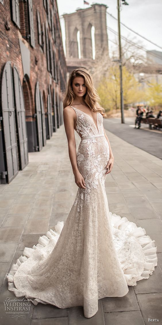 a mermaid wedding dress with lace appliques, a plunging neckline and a ruffled train by Berta