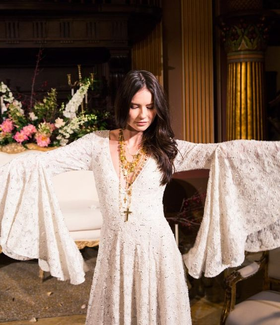 a gypsy-inspired wedding dress with a deep V-neckline, bell sleeves and embellishments