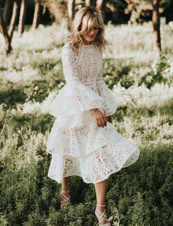 a lace wedding dress with a high neckline, bell sleeves and a layered skirt to stand out