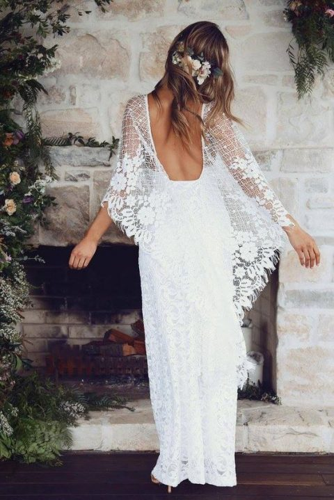 a boho lace wedding dress with a low back and wide bell sleeves