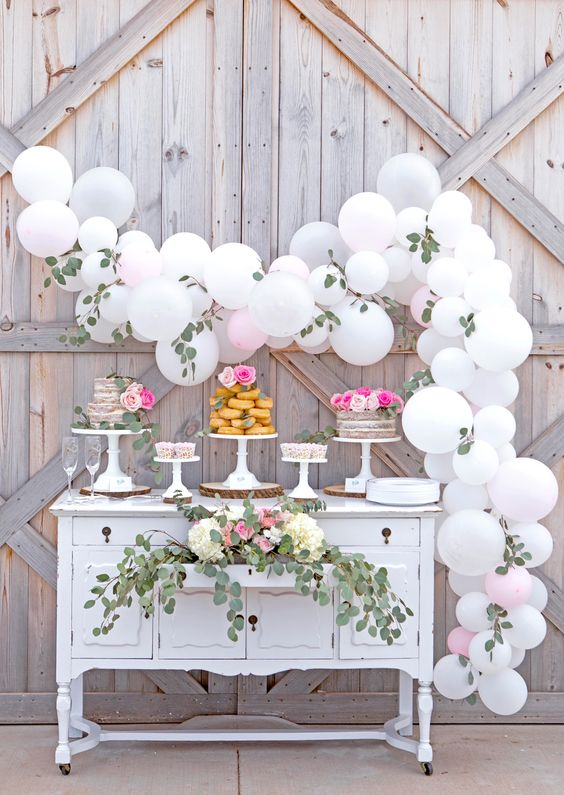 a white balloon and eucalyptus garland for making a dessert table backdrop