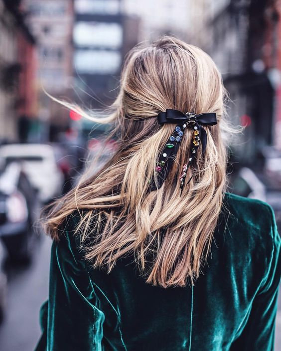 a half up ponytail is classics, it's accented with a floral black bow here