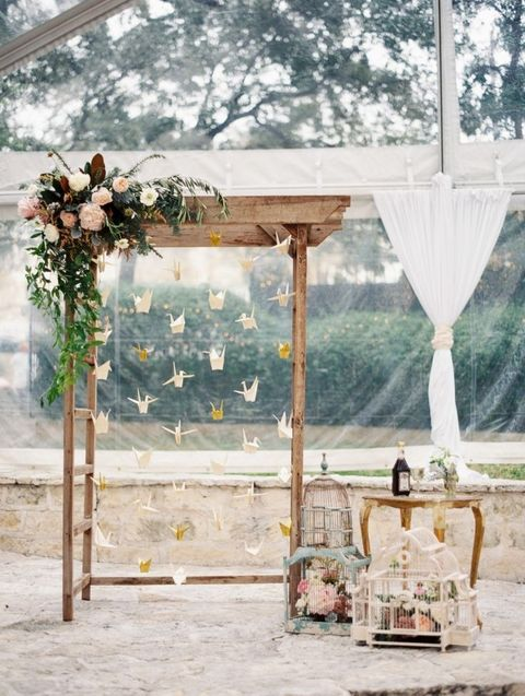 a wedding arch with lush greenery and blooms and hanging paper cranes, bird cages and blooms
