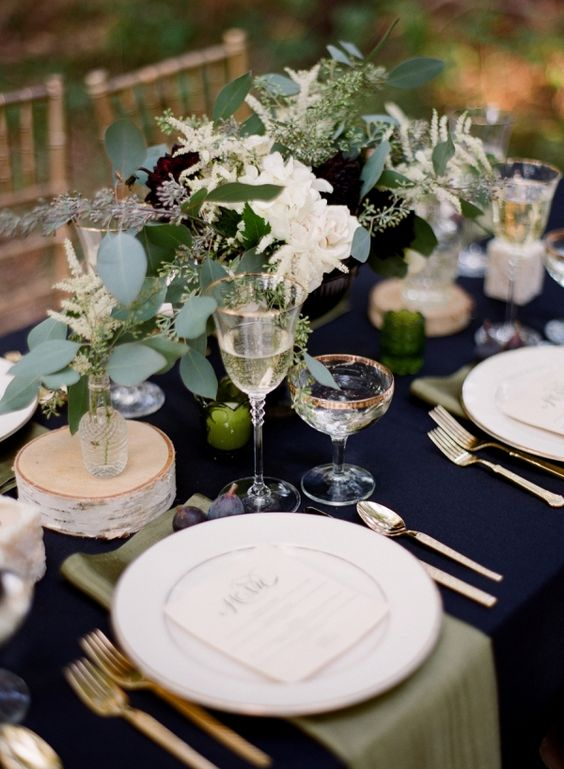 a navy tablecloth and gold cutlery create an elegant look, and lush greenery and blooms add a messy casual feel