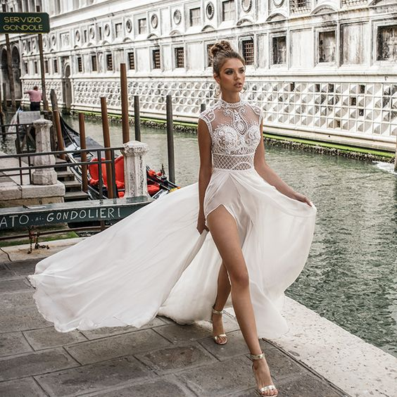 high neckline wedding dress with thigh high slits, a flowy skirt and an embellished and embroidered bodice by Julie Vino