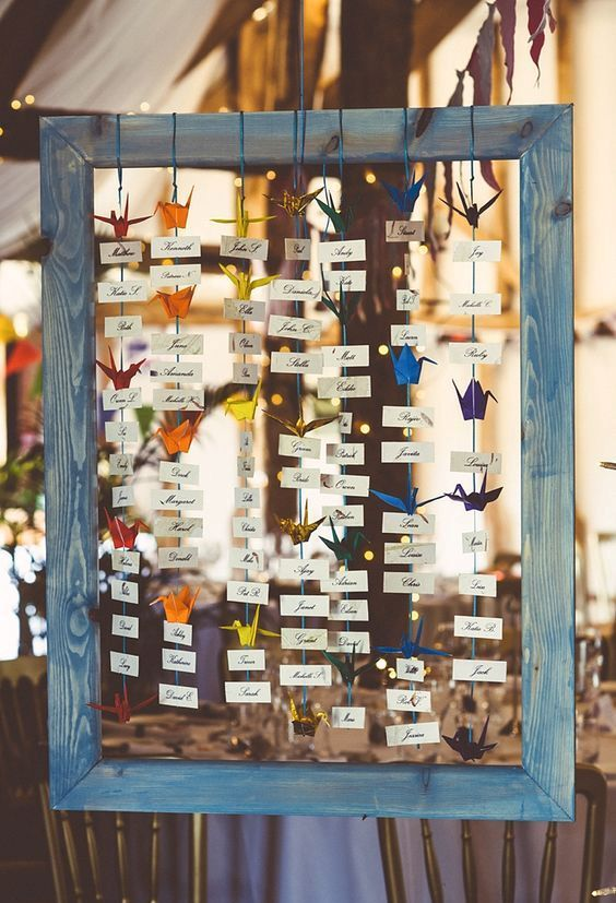 a seating plan of a wooden frame, cards and colorful paper cranes can be easily DIYed